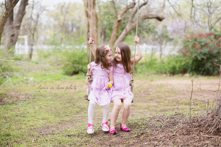 sisters in pink on tree swing in Family Outdoor Portraits at the Arlington studio by Lynn in Love Photo, Dallas and Houston Family Photographer