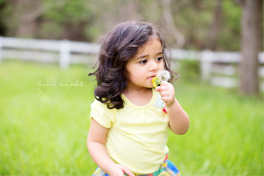 sweet indian girl smelling flowers in yellow shirt by Lynn in Love Photo, Dallas and Houston Child Photographer
